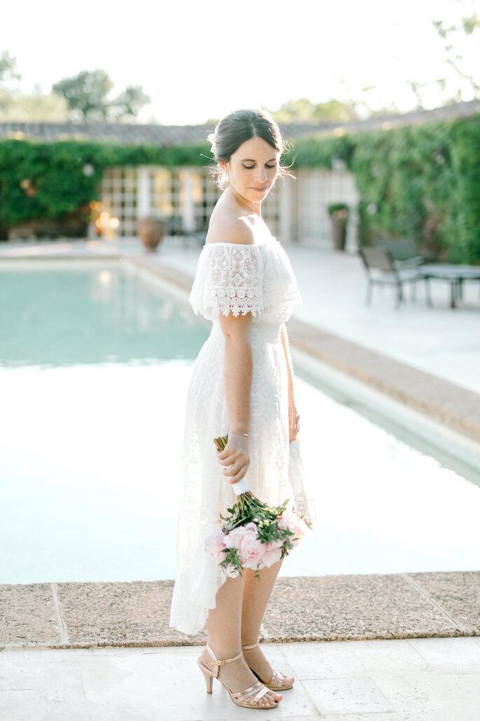 La mariée, bouquet à la main, prenant la pose dans les jardins du Pavillon Sully