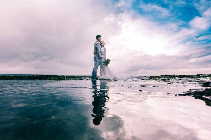 Deux mariés photographié au milieu d'un décor grandiose entre terre et mer