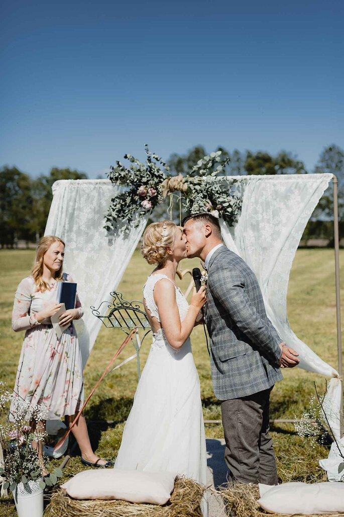 Vermählung. Brautpaar küsst sich vor de Altar