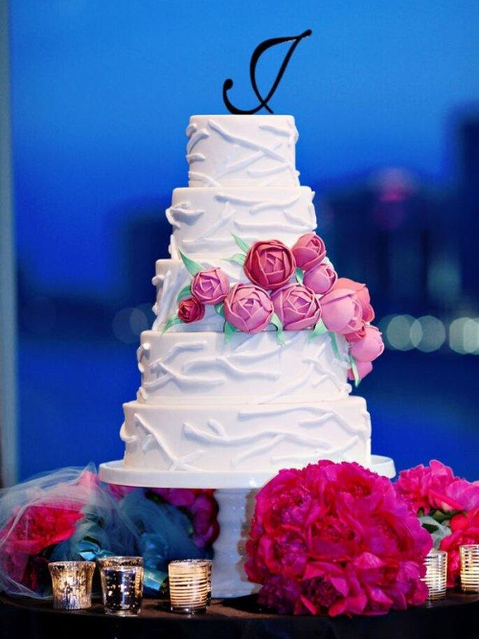 Pastel de boda blanco, con detalles de flores comestibles en rosa