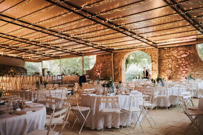 Salle de réception aux murs de pierres et aux grandes baies vitrées illuminée de guirlandes