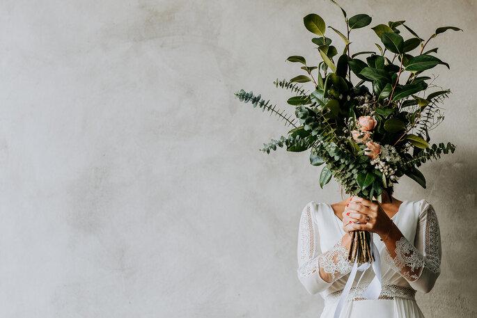 noiva com grande bouquet de flores à frente da cara