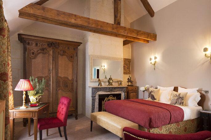 Une chambre du Château Laroche-Ploquin où l'on peut voir une armoire, un bureau et sa chaise, ungrand lit recouvert d'une couverture rouge, ou encore une cheminée d'époque.