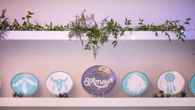 Décoration bohème épurée, avec des assiettes bleues, blanche et des plantes et guirlandes lumineuses au Domaine des Cormellas