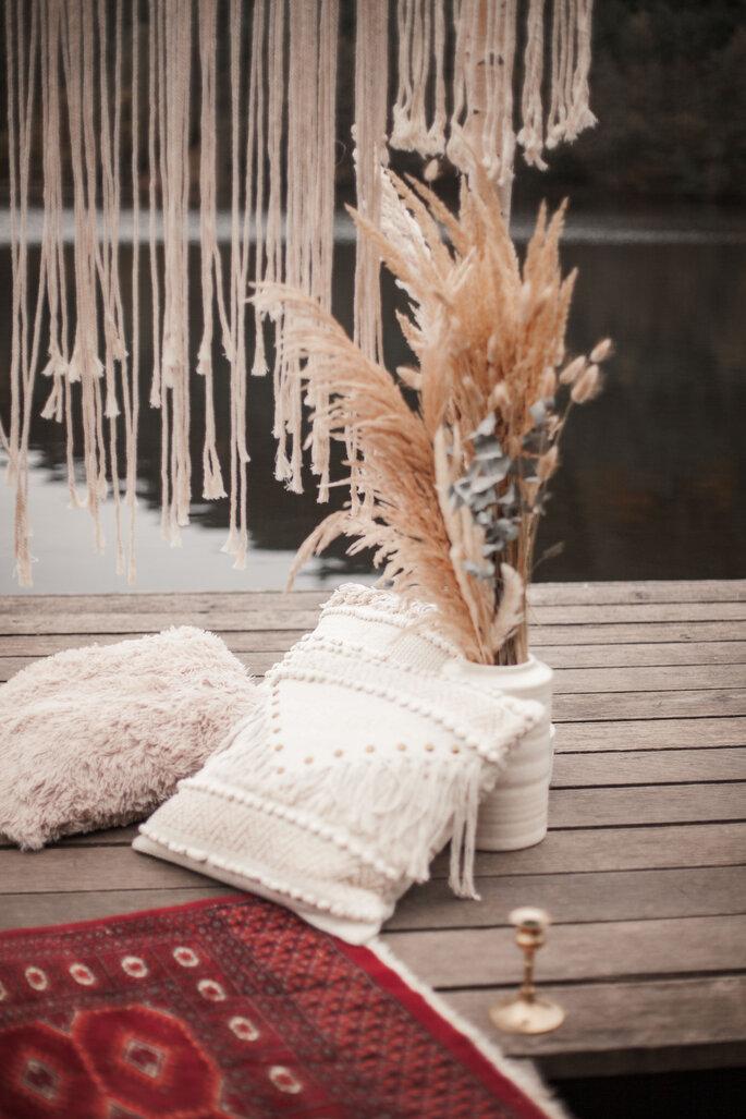 Ein Bootssteg, auf dem Teppiche, flauschige Teppiche und Pampasgras zu sehen sind.