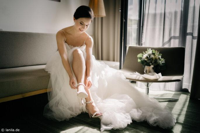 Braut in Brautkleid zieht sich Brautschuhe an