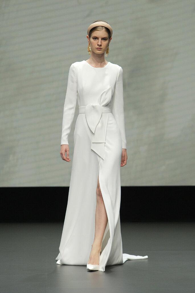 Colección Vestido de Novias 2021 Jesús Peiró vestido de novias entallado de mangas largas, cuello redondo, falda asimétrica, decorado con un cinturón con lazo y volantes