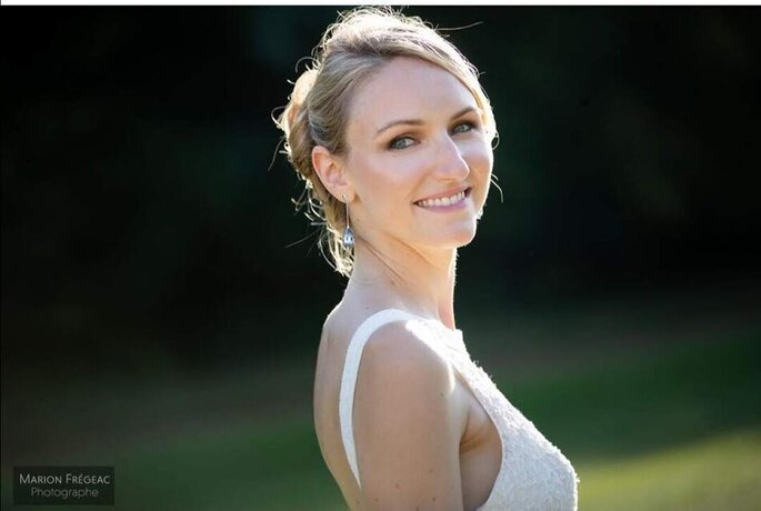 Une mariée portant un maquillage simple et naturel, arborant un grand sourire le jour de son mariage.