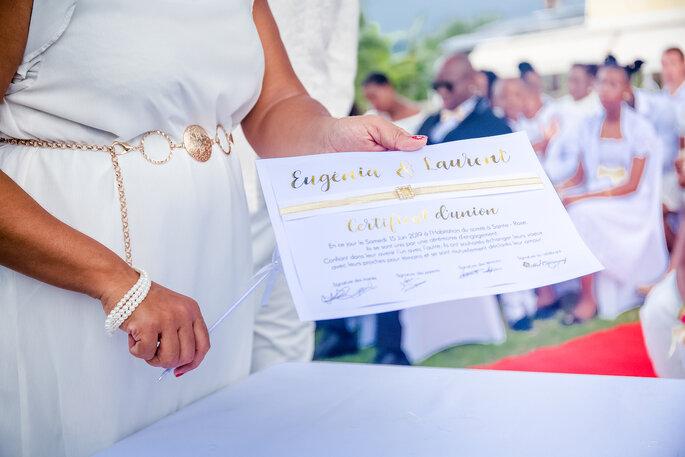 Une femme à une cérémonie en extérieur tenant un faire-part à la main.