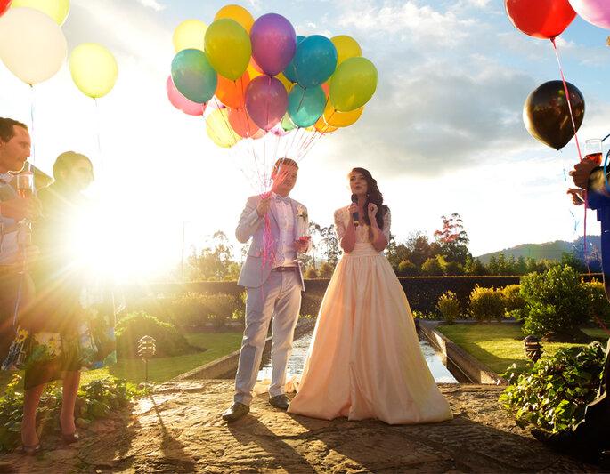 Esposos dando discurso y sosteniendo globos de colores
