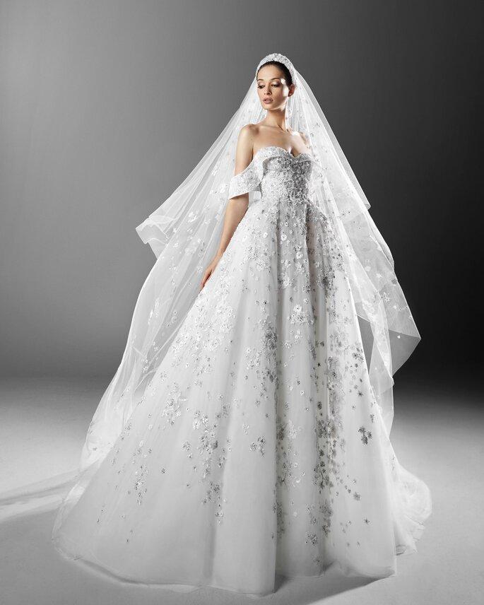 Zuhair Murad vestido de novia en corte princesa con hombros descubiertos, escote en corazón con decoración de bordado floral en el torso y en la falda amplia, con un velo en capas de transparencia con bordados florales.