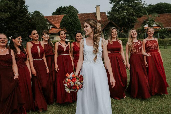 Noiva andando e madrinhas em vermelho atrás