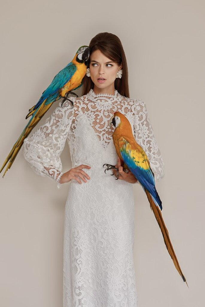 Une mariée porte une robe toute en dentelle avec des manches mousquetaires et un décolleté tout en transparence. 2 perroquets sont juchés sur elle