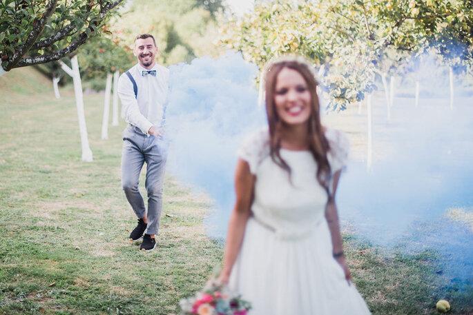 noiva em grande plano noivo atrás com fumos coloridos relvado campo