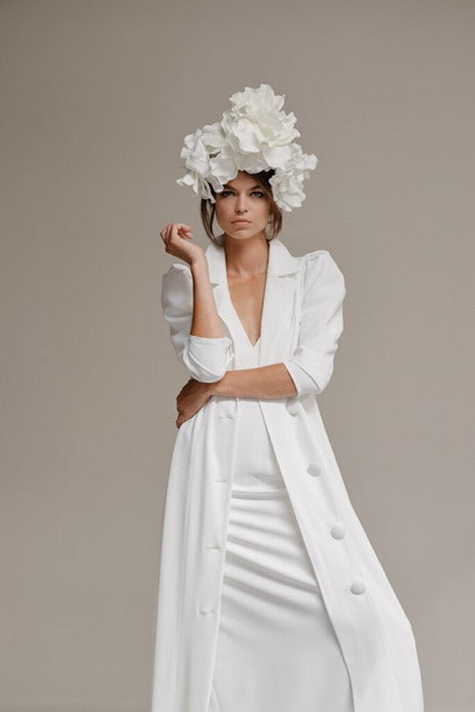 Une mariée portant une longue veste blanche à gros boutons et manches trois-quart sur une robe blanche avec une énorme couronne de fleurs blanche