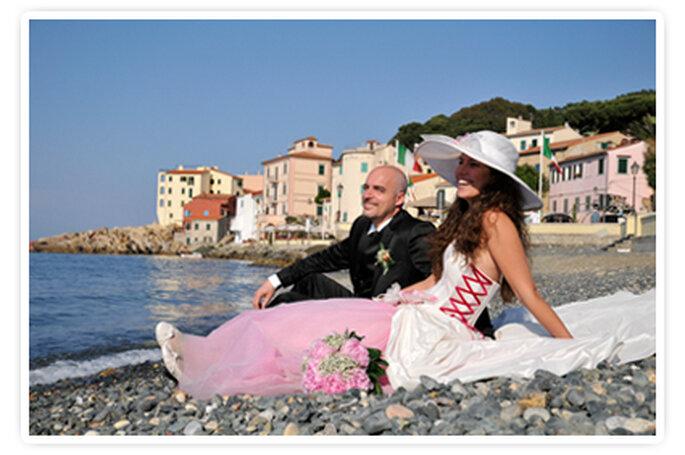 Gli sposi in riva al mare dell'isola d'Elba nel giorno del loro matrimonio. Foto New Image Officina d'Immagine