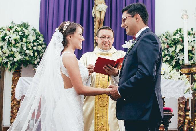 Sacerdote oficiando la boda con los novios tomados de la mano