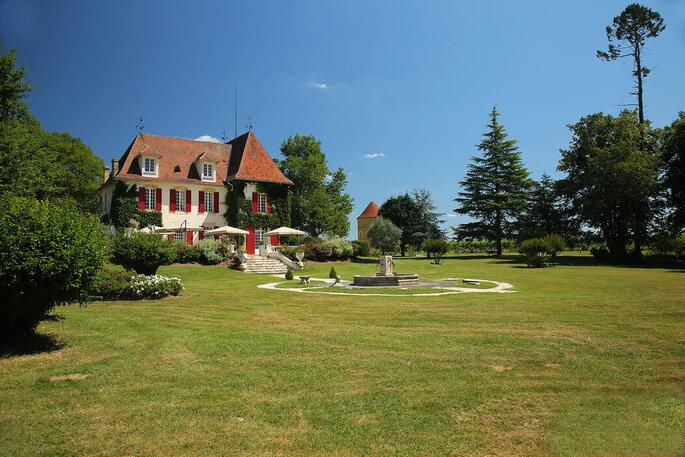 Le jardin du Château la Tilleraie habillé de grands séquoias et d'une fontaine au coeur du parc.