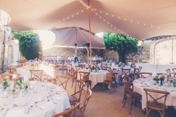Les tables de la réception d'un mariage en extérieur, sous des tonnelles ornées de lampions