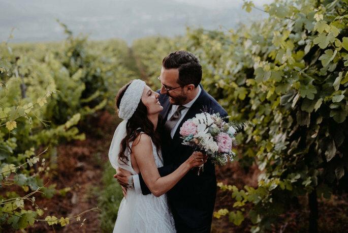 dois noivos agarrados com um bosque como fundo
