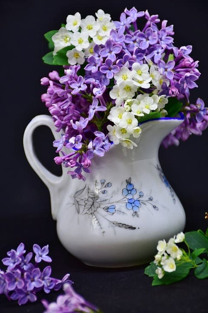 Arreglo de mesa con flores moradas y blancas en jarra de cerámica