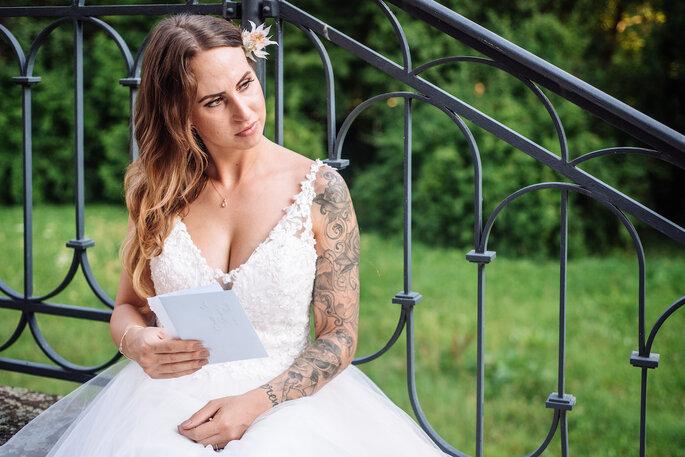 Die Braut sitzt auf einer Treppe und liest ihre Traurede.