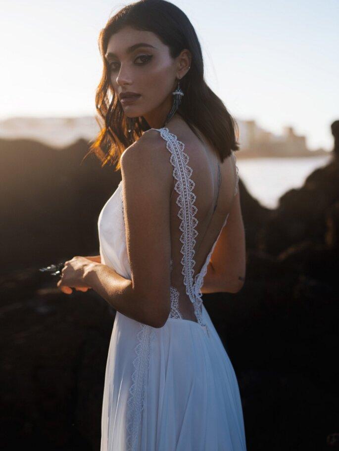 Anges et Rêves Mariage - Un mannequin portant une robe de mariée blanche fluide avec un beau dos nu