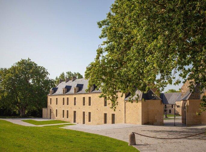 Façade du Domaine de la Cour des Lys avec une partie de son parc arboré en arrière-plan.