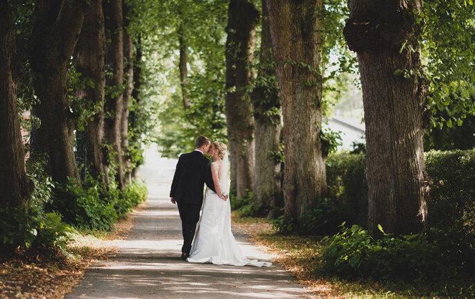 Brautpaar küssend in Allee
