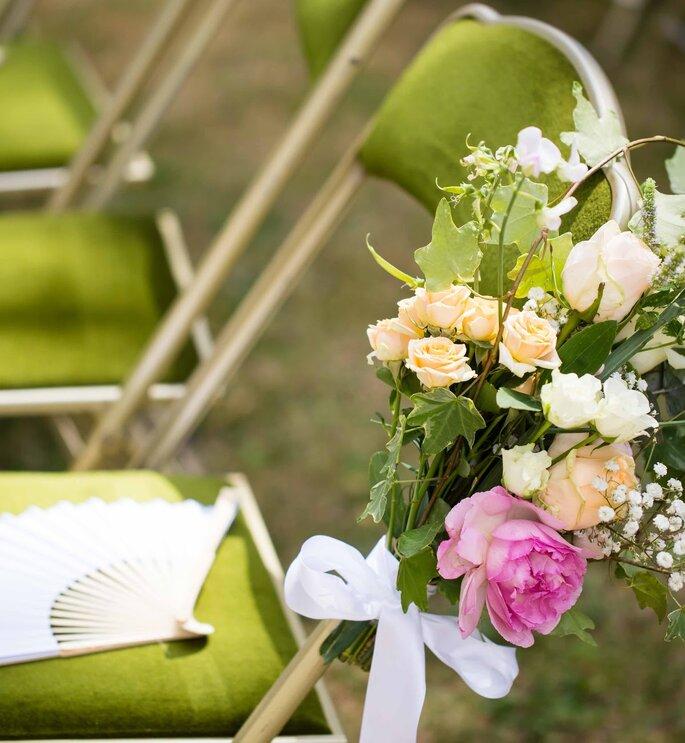 Les chaises pour les invités en extérieur sont ornées de bouquets de roses