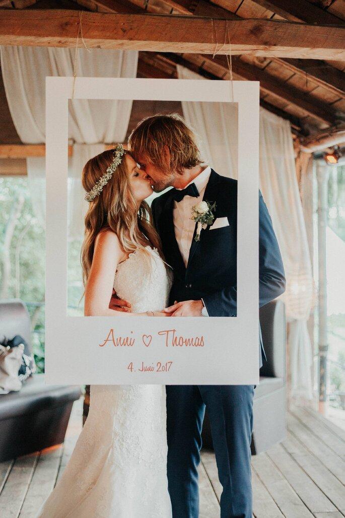 Das Brautpaar küsst sich in einem gebastelten Instagram-Rahmen bei der Boho-Hochzeit.