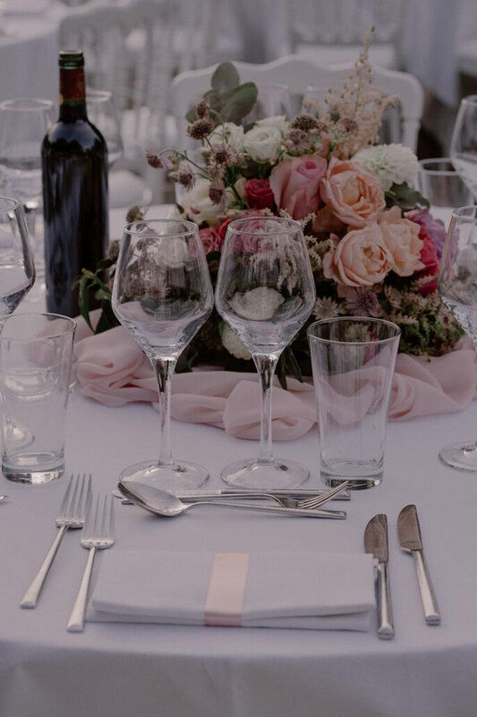 Table décorée pour un mariage, avec un bouquet de roses aux couleurs pastels, une nappe et des serviettes blanches pour une ambiance romantique