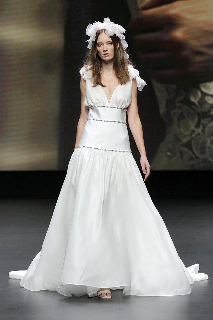 Vestido de novia corte imperial moderno con cintos de pedrería, escote en V y tirantes con moños
