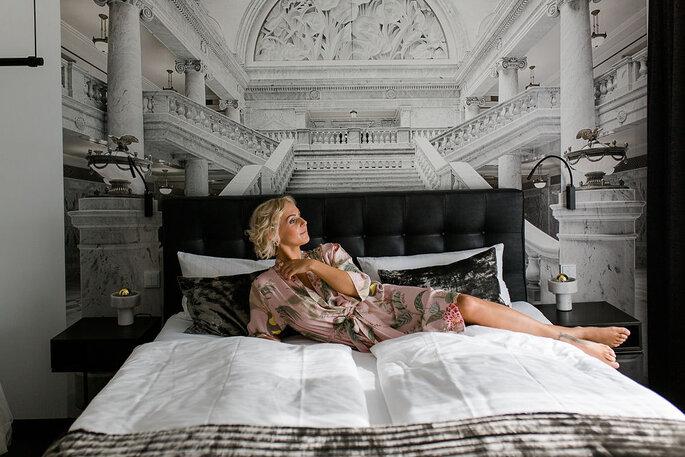 Die Braut liegt auf einem großen Bett, im Hintergrund ist ein antikes Treppenhaus zu sehen. Sie trägt einen Morgenmantel in Rosétönen.