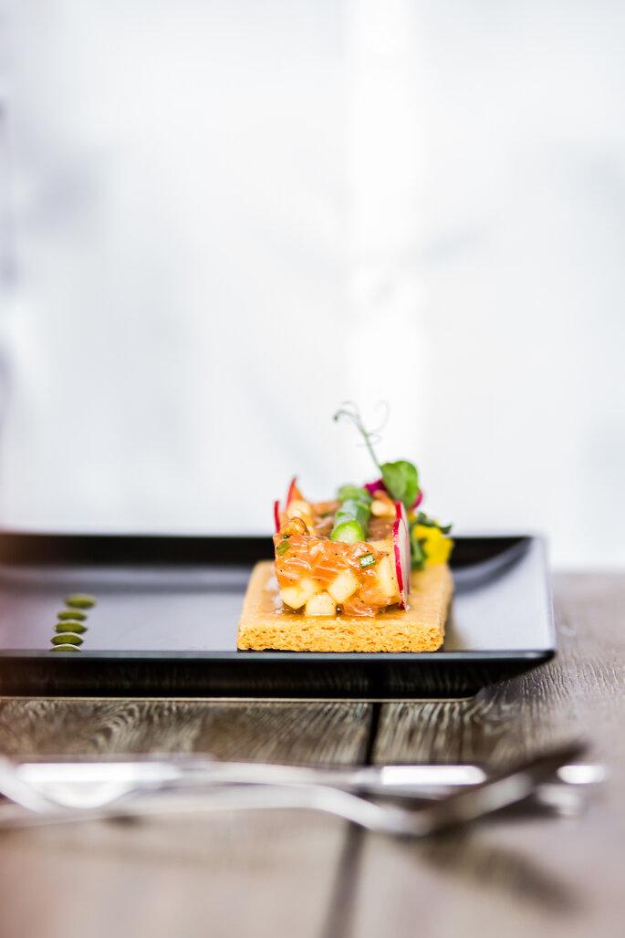 Canapé de saumon et asperges sur un cracker, présenté au milieu d'une assiette noire