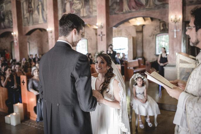 Novia mirando emocionada al novio ante la mirada del padre e invitados