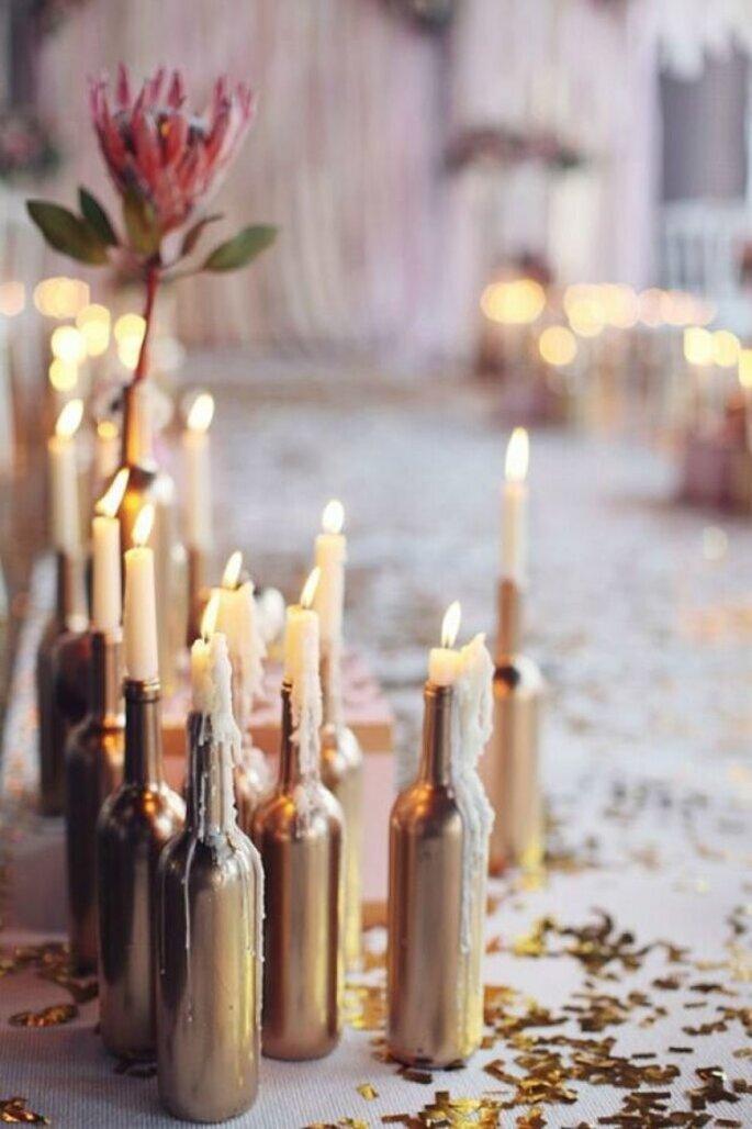 Lange weiße Kerzen stehen angezündet in Flaschen auf dem Boden