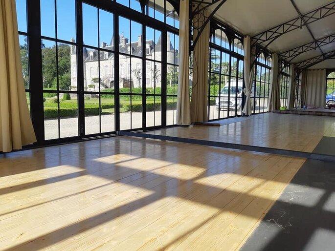 Salle de réception avec du parquet et de grandes baies vitrées où organiser bal et dîner de mariage