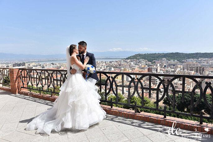 Ein Brautpaar küsst sich vor einer Großstadt-Kulisse.