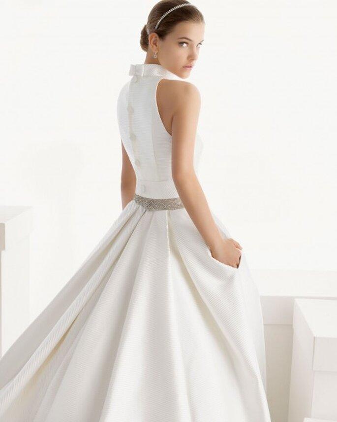 Vestido de novia con bolsas con detalle de moño en la espalda, cauda larga y cinturón de pedrería - Foto Rosa Clará