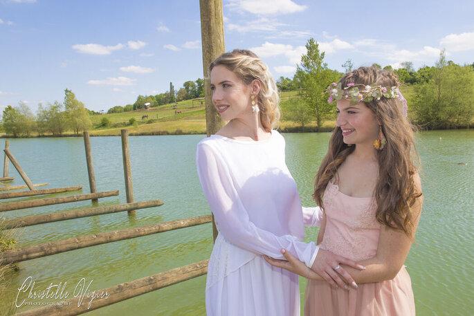 La mariée et l'une de ses demoiselles d'honneur devant le lac naturel du domaine.