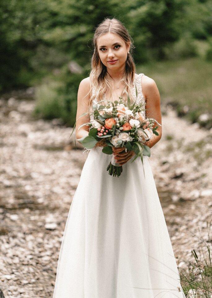 Nahe Frontalaufnahme der Braut mit ihrem Strauß