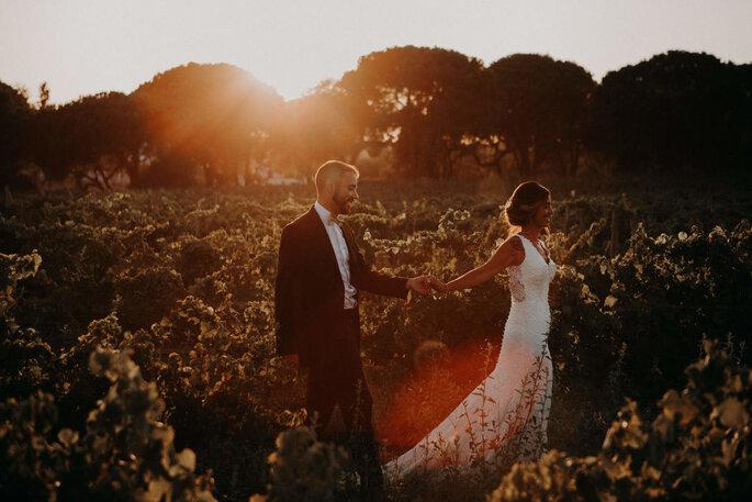 Noivos a caminhar no campo ao por-do-sol