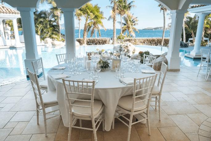 Une table est dressée pour un mariage dans une villa au bord d'une piscine avec une vue sur l'océan