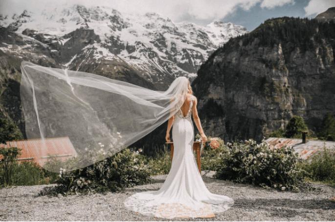 Braut steht draußen vor einem Berg