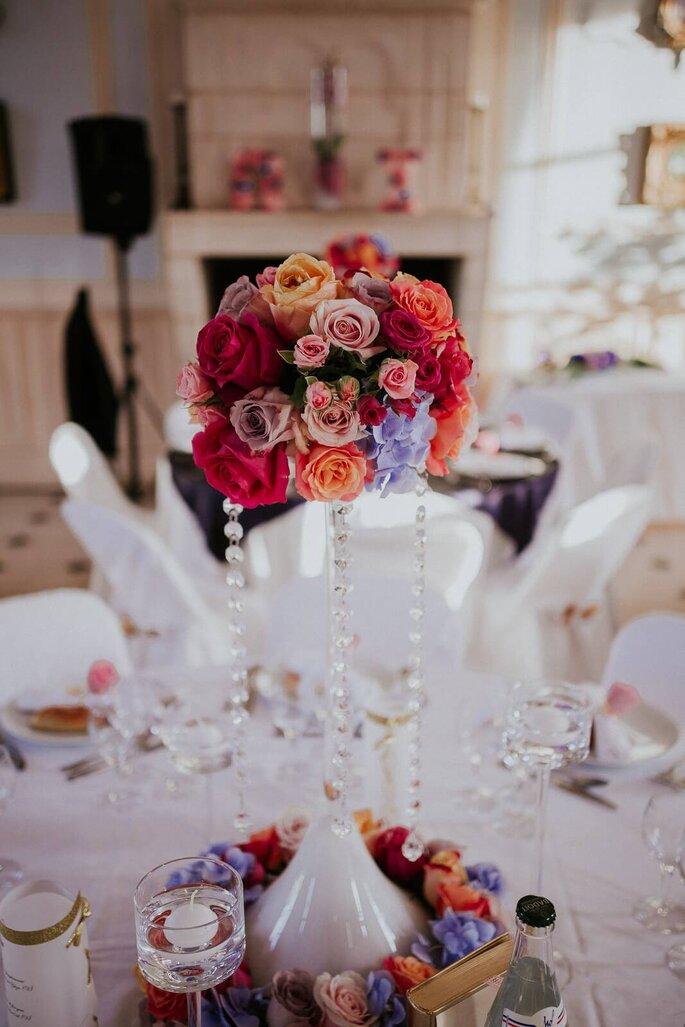 Sublime bouquet de roses colorées disposée sur une table décorée pour un mariage dans la salle de réception du Château de Denonville