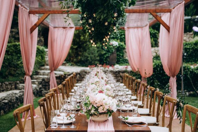 Réception champêtre en extérieure, table fleurie et décorée de rose, entourée de voilages décoratifs
