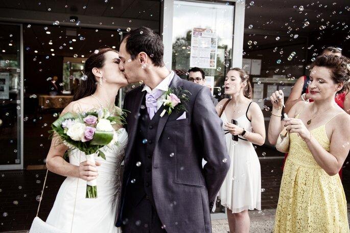 Les mariés s'embrassent tendrement à la sortie de la cérémonie, entourés de bulles de savons
