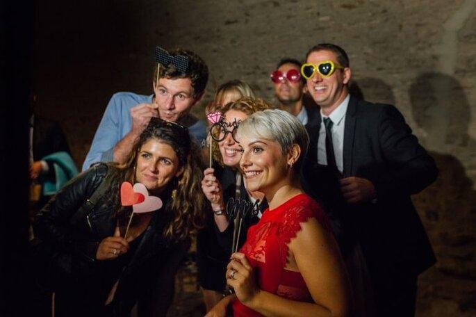 EWA - Photographies de mariage - Gironde - Un groupe d'invités posant avec plein d'accessoires différents lors d'un mariage