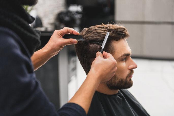 homem a ser penteado barbeiro cabeleireiro